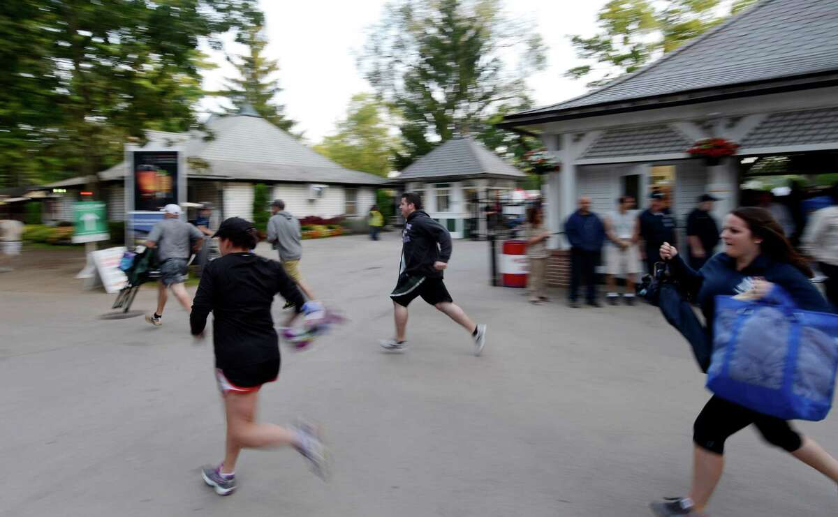 Racing patrons run to stake claim to a picnic table as the gates open at 7:00 am on Travers Day at the Saratoga Race Course in Saratoga Springs, N.Y. Aug. 25, 2012. (Skip Dickstein/Times Union)