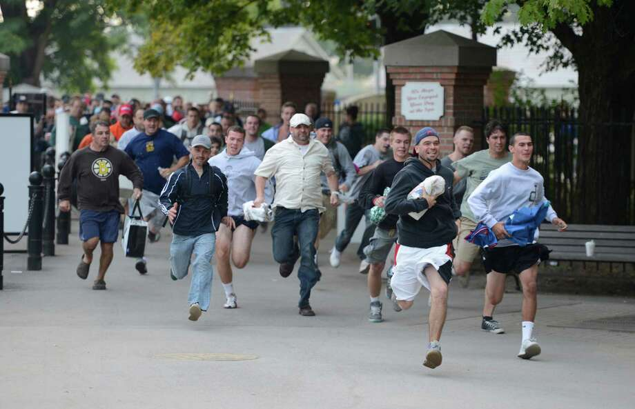 Racing patrons run to stake claim to a picnic table as the gates open at 7:00 am on Travers Day at the Saratoga Race Course  in Saratoga Springs, N.Y. Aug. 25, 2012.   (Skip Dickstein/Times Union) Photo: Skip Dickstein / 00018972A