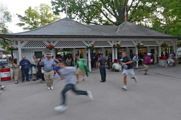 Racing patrons run to stake claim to a picnic table as the gates open at 7:00 a.m. on Travers Day at the Saratoga Race Course  in Saratoga Springs, N.Y. Aug. 25, 2012.   (Skip Dickstein/Times Union) Photo: Skip Dickstein / 00018972A