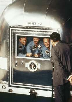 """FILE - In this July 24, 1969 file photo, President  Richard Nixon, back to camera, greets the Apollo 11 astronauts in the quarantine van on board the U.S.S. Hornet after splashdown and recovery.   The Apollo 11 crew from left:  Neil Armstrong, Michael Collins, and Edwin """"Buzz"""" Aldrin. Photo: AP / AP"""