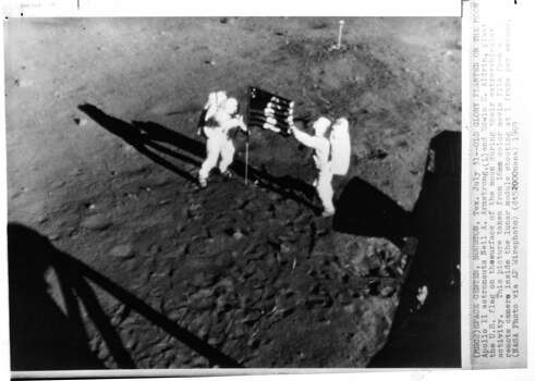 Apollo 11 Astronauts Neil A. Armstrong, (L), and Edwin E. Aldrin, plant the U.S. flag on the surface of the moon during their extravehicular activity. This picture taken from 16mm color movie film from a remote camera inside the lunar module shooting a 1 frame per second. Photo: NASA Via AP, AP / AP Wirephoto