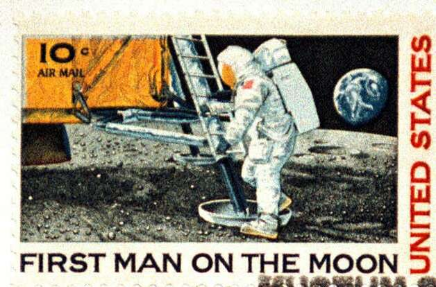 An original First Man on the Moon stamp is shown Tuesday, July 20, 1999, at the Neil Armstrong Air and Space Museum in Wapakoneta, Ohio. Stamps such as the one shown are on sale at the museum.  Tuesday, on the 30th anniversary of native son Neil Armstrong's first steps on the moon, the parking lot was full outside the museum that bears his name. Inside, the gift shop was doing a good business in model airplanes, T-shirts and pictures of Armstrong. Photo: NICK SHORT, AP / LIMA NEWS