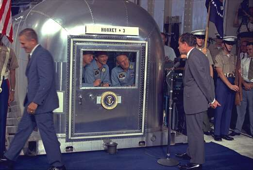 President Nixon views the Apollo 11 astronauts in the isolation unit aboard the USS Hornet after splashdown and recovery, in this July 24, 1969 file photo. July 20, 1999 marks the 30th anniversary of the landing on the moon by the Apollo II crew. The Astronauts, left to right, are:  Neil Armstrong,  Michael Collins and Edwin A. Aldrin. Photo: AP / AP