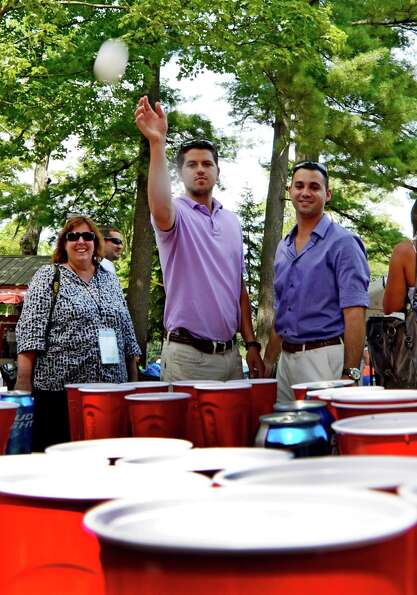 Ryan Jordan, left and Dean Chiusano enjoy a game of beer pong on Travers Day at the Saratoga Race Co