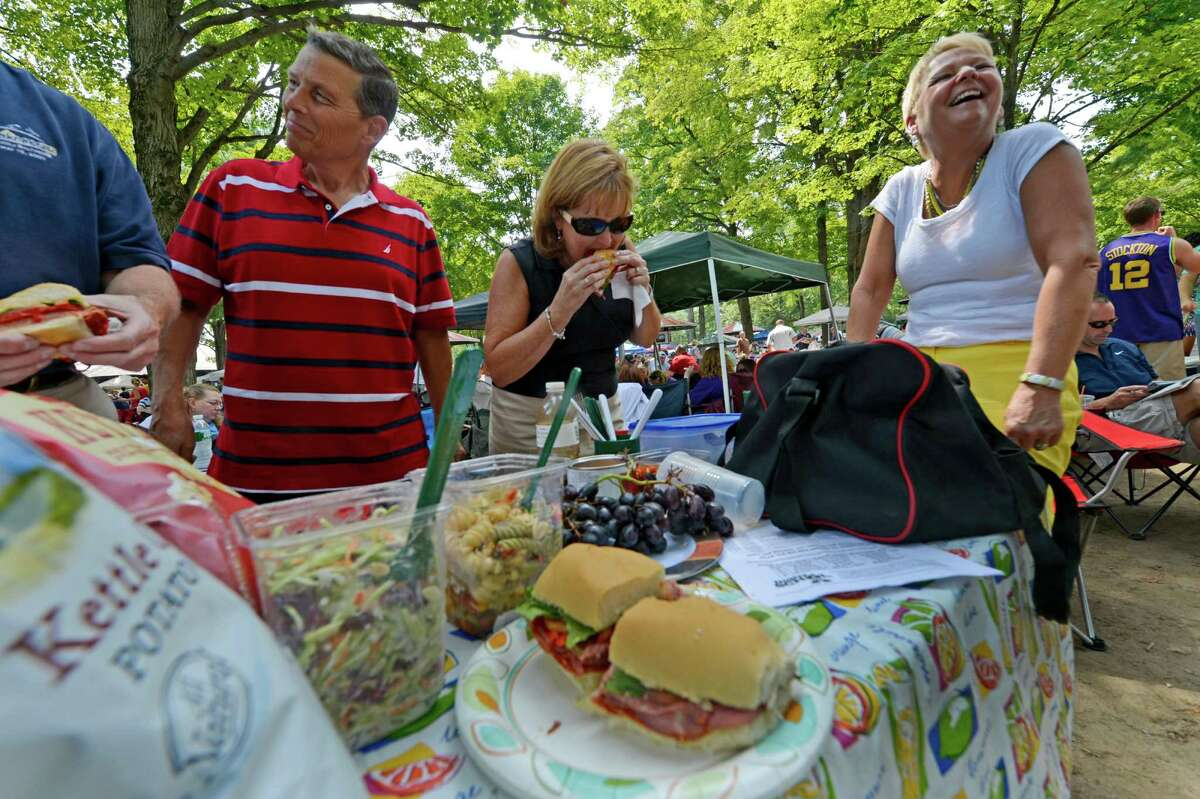 Food is everywhere in the picnic area as Tom Howe, left with wife Jane Howe and Judy DelCogliano enjoy food on Travers Day at the Saratoga Race Course in Saratoga Springs, N.Y. Aug. 25, 2012. (Skip Dickstein/Times Union)