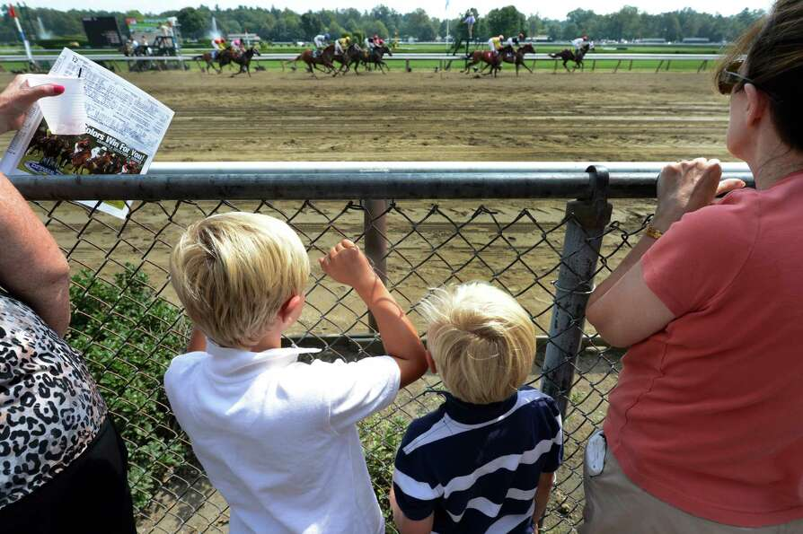 Tyler,7,  left and Owen Rodowicz, 4  of New Town Pa. enjoy the race action on Travers Day at the Sar