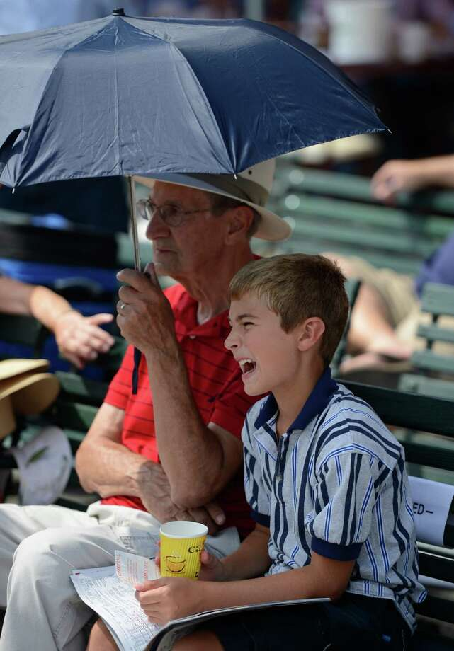 Robby Ciarla enjoys the shade from his grandfather Dominic Ciarla's umbrella as he reacts to his pick on Travers Day at the Saratoga Race Course  in Saratoga Springs, N.Y. Aug. 25, 2012.   (Skip Dickstein/Times Union) Photo: Skip Dickstein / 00019010A