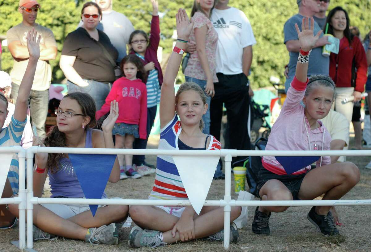 Crowd members raise their hands to volunteer during the Alaskan Pig Races.