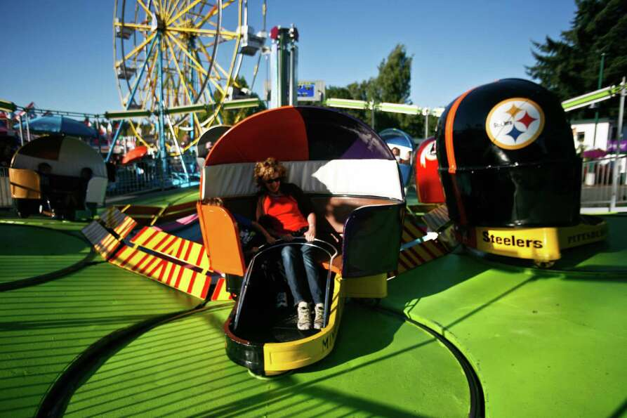 A woman rides the Tilt-A-Whirl.