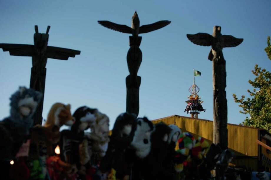 A ride is shown behind three totem poles. Photo: Sofia Jaramillo / SEATTLEPI.COM