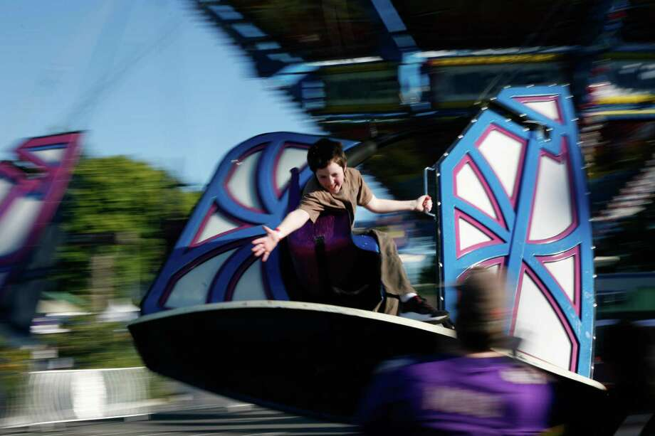 A boy reaches out to high-five his father while riding an amusement ride. Photo: Sofia Jaramillo / SEATTLEPI.COM