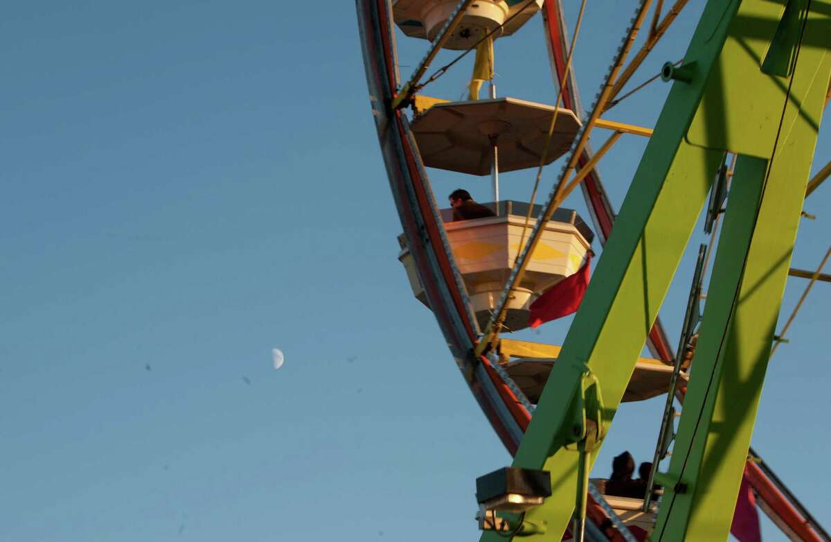 The moon is shown near the ferris wheel at the Evergreen State Fair in Monroe on Friday, Aug. 24, 2012.