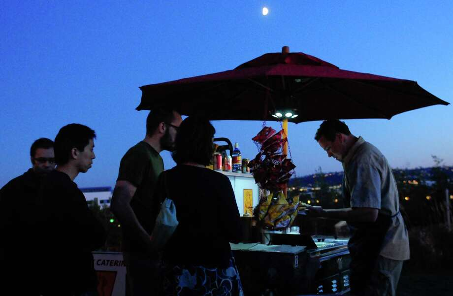 Marcel Hamlin serves up Dante's Inferno Dogs to attendees. Photo: LINDSEY WASSON / SEATTLEPI.COM