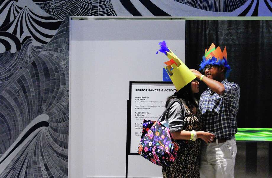 Kevin Africa, right, helps Samantha Garcia with her construction paper hat. Photo: LINDSEY WASSON / SEATTLEPI.COM