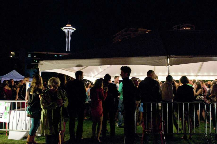 People gather under a tent to enjoy drink, conversation and the music of DJ Riz. Photo: LINDSEY WASSON / SEATTLEPI.COM