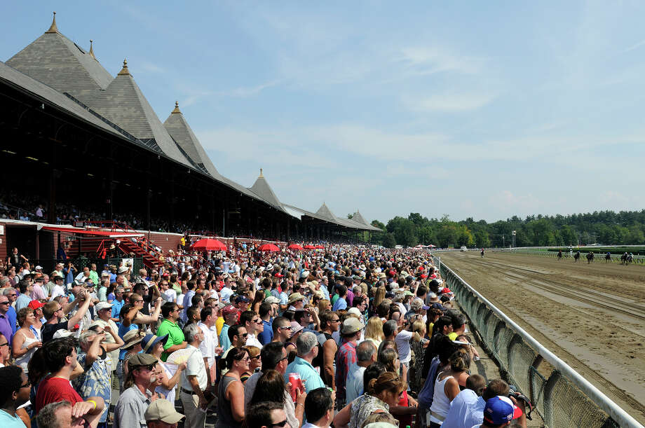 Race fans watch Honorable Dillion with jockey Jose Lezcano win the second race of the day, leading up to the 143rd Travers Stakes at Saratoga Race Course in Saratoga Springs, N.Y., Saturday, Aug. 25, 2012. (AP Photo /Hans Pennink) Photo: Hans Pennink