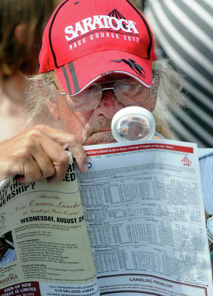 Bill Weigand of Lennox, Mass., looks at a racing program before the 143rd Travers Stakes horse race
