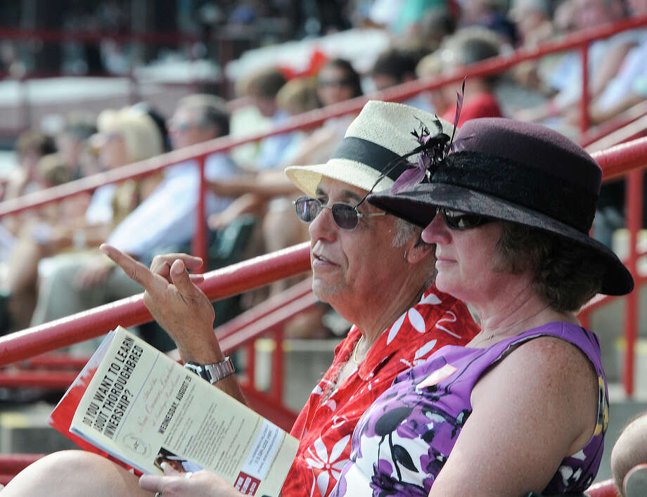 Peter Pius and his wife Susan Pius of Rhinebeck, N.Y., watch horse racing prior to the 143rd Travers Stakes at Saratoga Race Course in Saratoga Springs, N.Y., Saturday, Aug. 25, 2012. (AP Photo /Hans Pennink) Photo: Hans Pennink