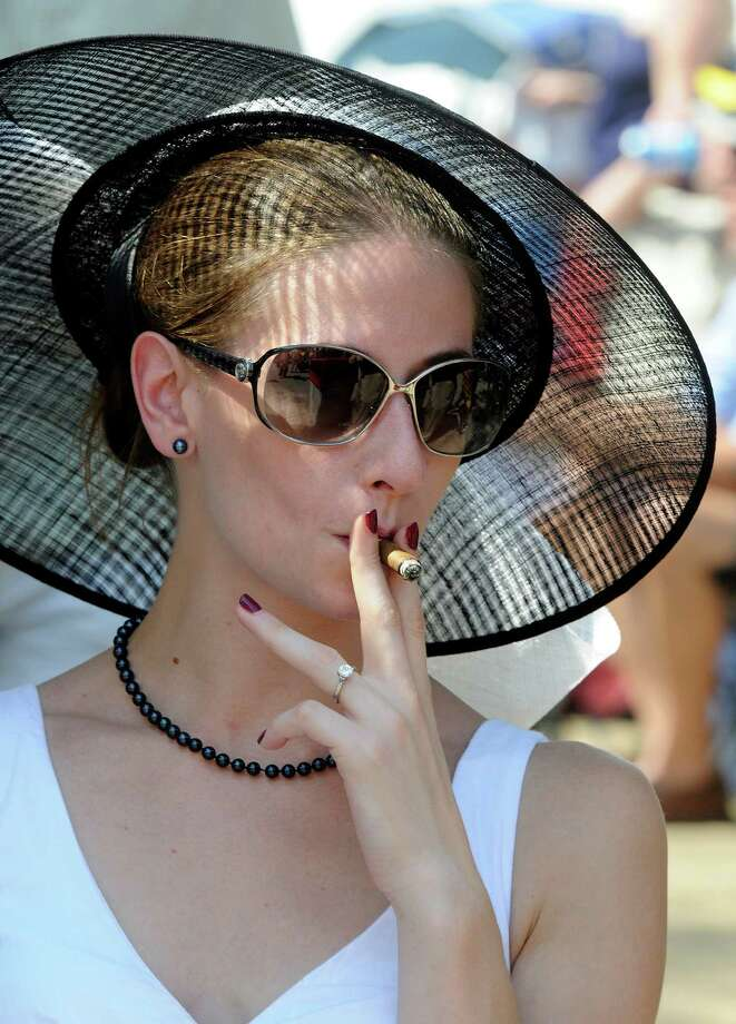 Carly Bristol of Colonie, N.Y., smokes a cigar while watching event prior to the 143rd Travers Stakes horse race at Saratoga Race Course in Saratoga Springs, N.Y., Saturday, Aug. 25, 2012. (AP Photo /Hans Pennink) Photo: Hans Pennink