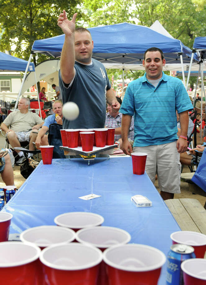John Robinson, left, of Saratoga Springs, N.Y., and John Murray of Albany, N.Y., play beer drinking games while watching other races before the 143rd Travers Stakes at Saratoga Race Course in Saratoga Springs on Saturday, Aug. 25, 2012. (AP Photo /Hans Pennink) Photo: Hans Pennink