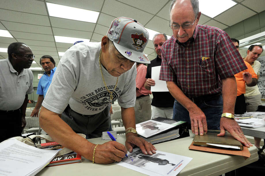 Gilbert Hernandez Black signs a copy of a 1956 photo of himself when he played for the Negro American League's Indianapolis Clowns after speaking at the Danbury Museum & Historical Society on Thursday, Aug. 23, 2012. Redding resident, Thomas Urwin, right, graduated with Black from Stamford High School in 1954. Urwin said he skipped supper to see his classmate. Photo: Jason Rearick / The News-Times