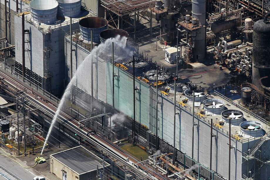 Firefighting crews keep pouring water onto a unit after a fire at a Chevron's refinery in Richmond, Calif., on, Aug. 7. The blaze prompted thousands of nearby residents to seek assistance at hospital emergency rooms. Photo: Aric Crabb / Oakland Tribune