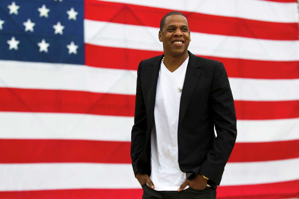"""FILE - In this May 14, 2012 file photo, entertainer Shawn """"Jay-Z"""" Carter smiles in between interviews, after a news conference at Philadelphia Museum of Art in Philadelphia. The city where America was made is gearing up for rapper Jay-Z's """"Made In America"""" music festival, which officials estimate will attract 100,000 fans to Philadelphia over Labor Day weekend, Sept. 1-2, 2012 (AP Photo/Matt Rourke, file)"""