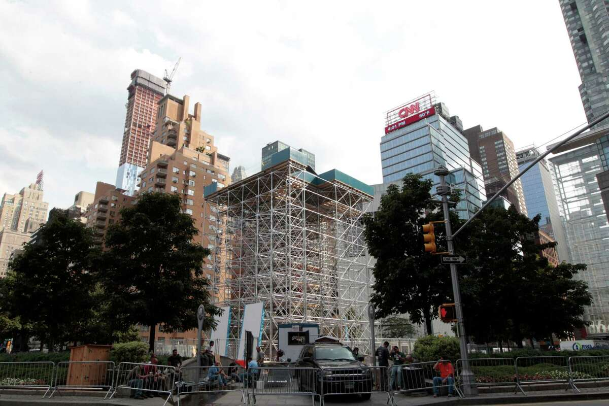 """Scaffolding surrounds the statue of Christopher Columbus, Tuesday, Aug. 21, 2012 in New York's Columbus circle. Japanese artist Tatzu Nishi is constructing ?""""Discovering Columbus,?"""" a contemporary living room around a statue of Columbus as a way to intimately engage the public with the iconic figure which looms six stories above a busy intersection of mid-Manhattan. But some Italian-Americans say the art project makes a mockery of the great explorer and trivializes history. (AP Photo/Mary Altaffer)"""