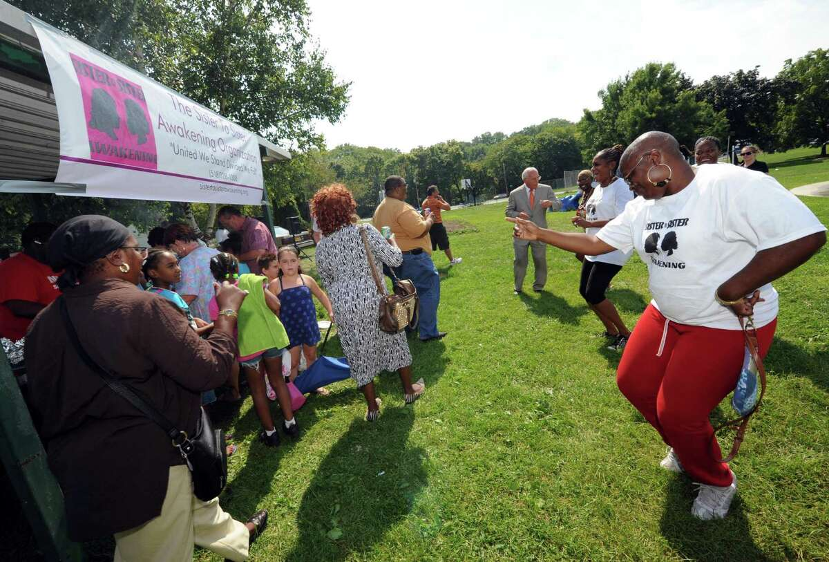 Ri-na Yarmeto, right, joins others in dance during the 2nd Annual Remembering The Fallen Stars community picnic at Krank Park in Albany, NY Saturday Aug. 25, 2012. (Michael P. Farrell/Times Union)