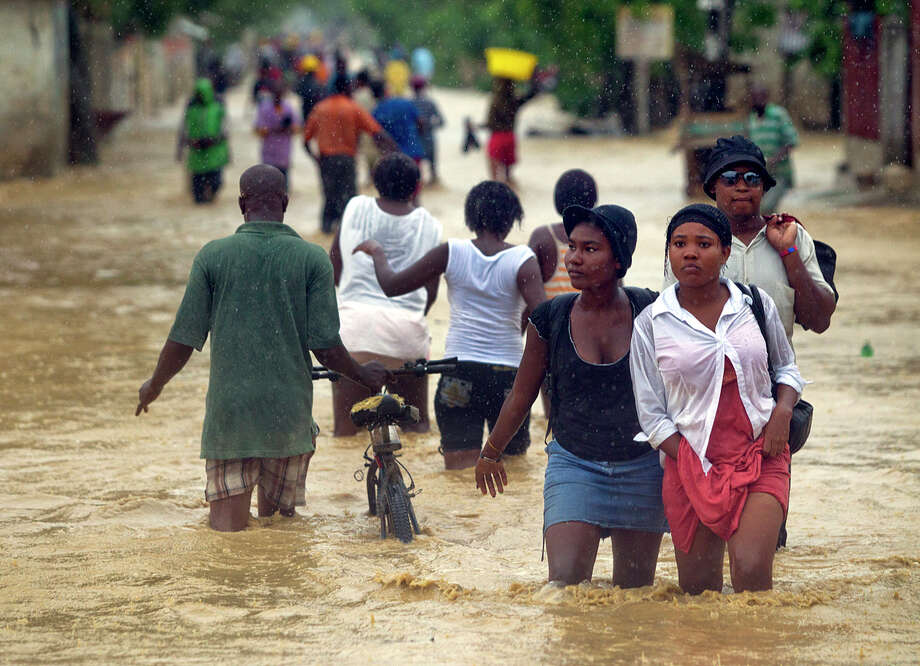 1265 x 916~~$~~Residents of Cite Soleil, Haiti, wade through floodwaters on Route Neuf from Tropical Storm Isaac, Saturday, Aug. 25, 2012. Isaac pushed into Cuba on Saturday after sweeping across Haiti's southern peninsula, where it caused flooding and at least three deaths, adding to the misery of a poor nation still trying to recover from the terrible 2010 earthquake. Photo: Patrick Farrell, AP / The Miami Herald