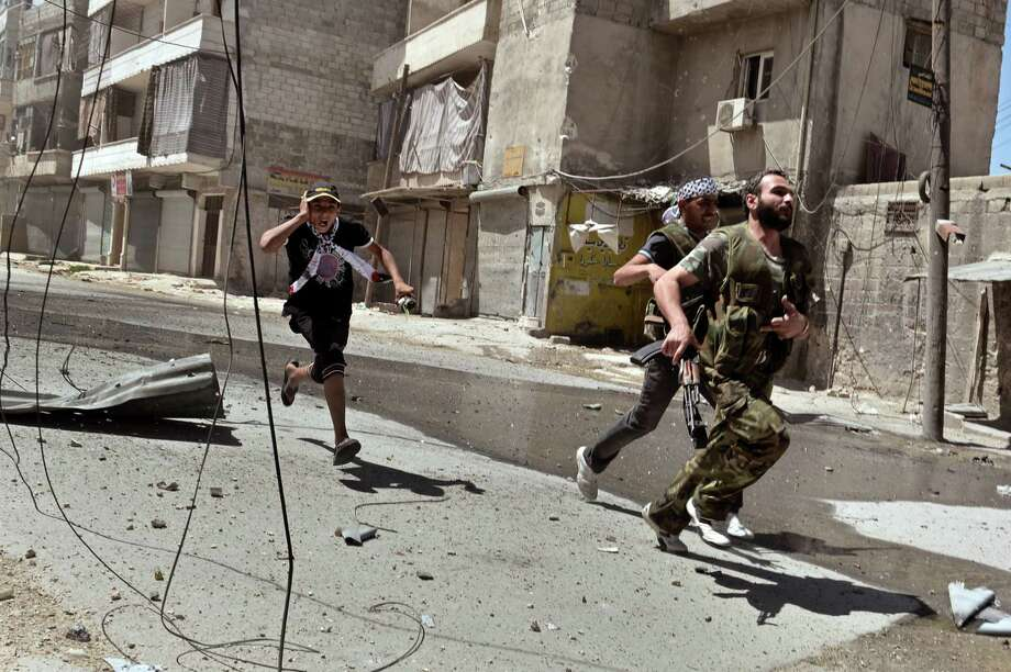 "Rebel fighters run for cover during battle against Syrian government forces at the al-Mashad neighbourhood in the northern Syrian city of Aleppo on August 25, 2012.  Syrian rebels say they are digging in for a war of attrition in Aleppo, where what was being billed as the ""mother of all battles"" is now dragging on into a second month of bloody stalemate.  AFP PHOTO / ARIS MESSINISARIS MESSINIS/AFP/GettyImages Photo: ARIS MESSINIS, AFP/Getty Images / AFP"