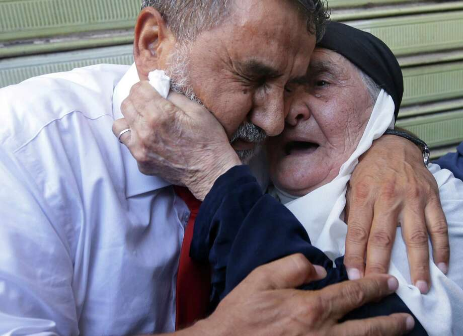 RETRANSMISSION FOR ALTERNATIVE CROP -- Hussein Ali Omar, 60, one of 11 Lebanese Shiite pilgrims that Syrian rebels have been holding for three months in Syria, hugs his mother, right, upon arrival at his house in the southern suburb of Beirut, Lebanon, 2012. Syrian rebels freed Omar on Saturday in a move aimed at easing cross-border tensions after a wave of abductions of Syrian citizens in Lebanon. The Shiite pilgrims were abducted May 22 after crossing into Syria from Turkey on their way to Lebanon. (AP Photo/Hussein Malla) Photo: Hussein Malla, Associated Press / AP
