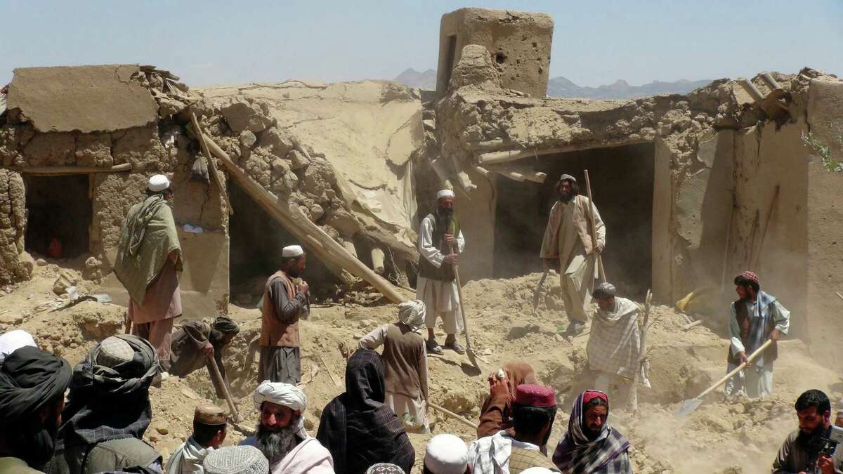 FILE - In this Wednesday, June 6, 2012 file photo, Afghan villagers gather near a house destroyed in an apparent NATO raid in Logar province, south of Kabul, Afghanistan. It was once President Barack Obama's