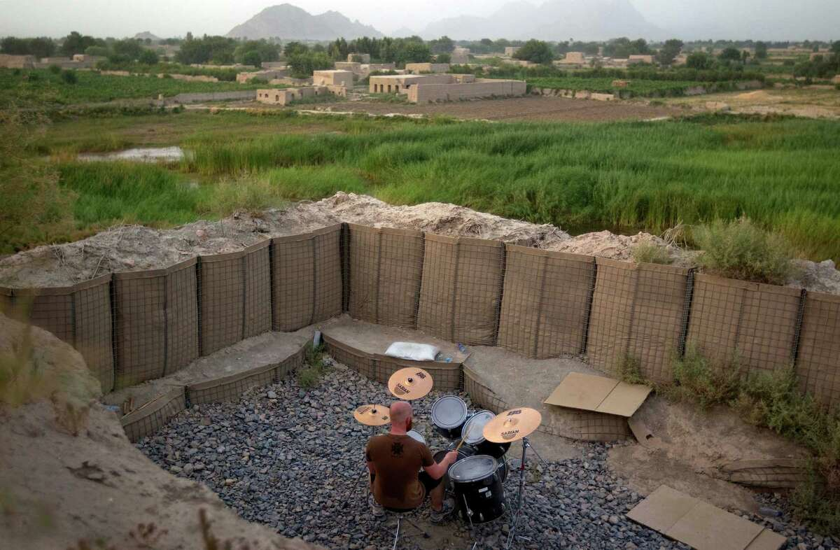 FILE -In this June 24, 2011 file photo, Canadian Forces soldier, Cpl. Ben Vandandaigue, plays on a drum kit on Forward Operating Base Sperwan Ghar overlooking the Panjwaii district of Kandahar province, Afghanistan. It was once President Barack Obama's