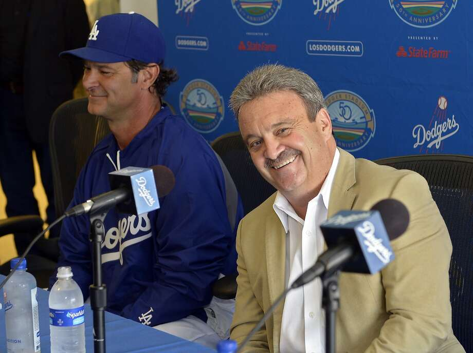 Ned Colletti (right, with manager Don Mattingly) made deals as GM to put together a team that's close to an NL West championship. Now he's in the background as a senior adviser. Photo: Mark J. Terrill, Associated Press
