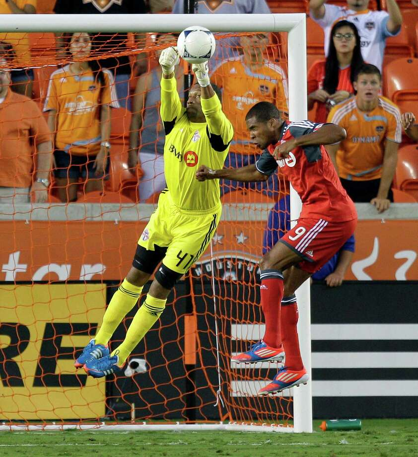 Goalkeeper Freddy Hall of Toronto FC knocks the ball away as teammate Ryan Johnson also defends. Photo: Bob Levey, Getty Images / 2012 Getty Images
