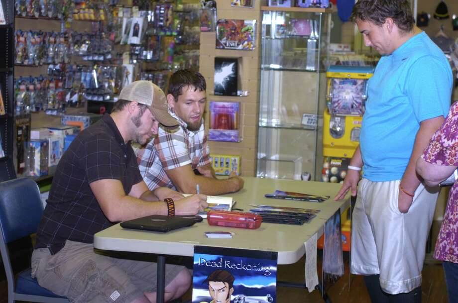 """Danny Allain signs a copy of his comic book, """"Dead Reckoning, for Noah Mathews, 16, of Bridge City. Allain was at All Star Comics in Nederland on Saturday to promote his book, part one of a series. Photo: Sarah Moore"""