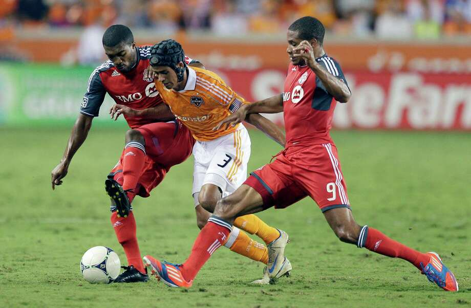 Calen Carr attempts to dribble the ball through Ashtone Morganof the Toronto FC and Ryan Johnson in the second half. Photo: Bob Levey, Getty Images / 2012 Getty Images