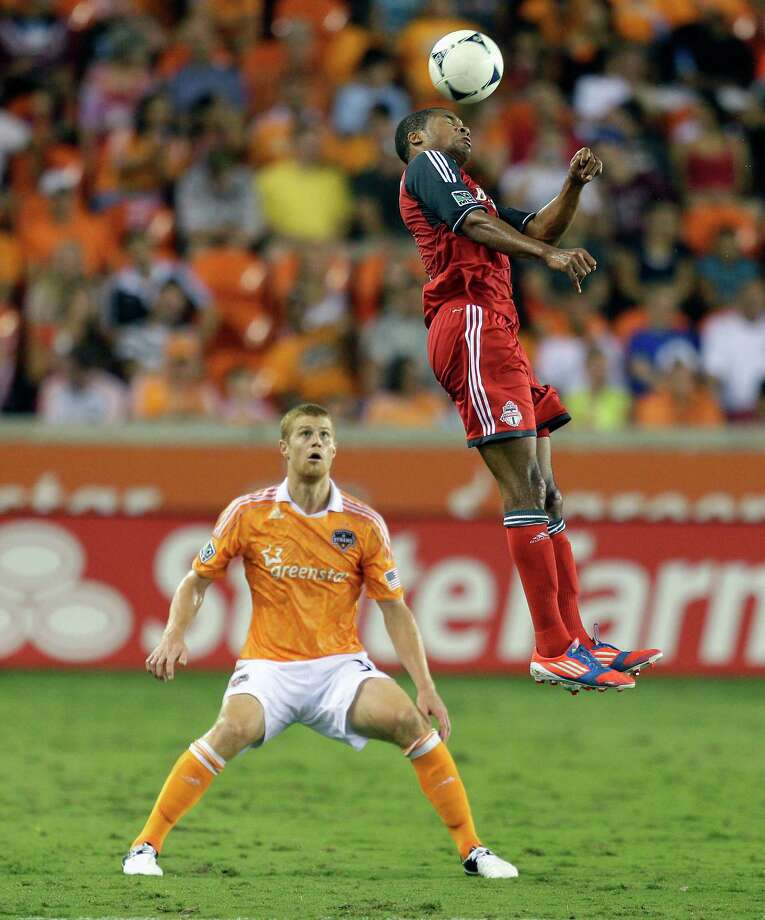 Ryan Johnson heads the ball away from Andre Hainault in the second half. Photo: Bob Levey, Getty Images / 2012 Getty Images