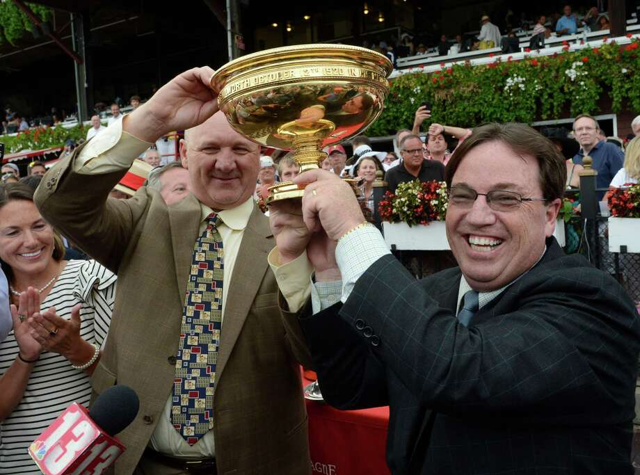 Winning trainers Kenny McPeek, Golden Ticket, left and Kiaran McLaughlin, Alpha share the winner's trophy after a dead heat in the 143rd running of The Travers Stakes  at the Saratoga Race Course  in Saratoga Springs, N.Y. Aug. 25, 2012.   (Skip Dickstein/Times Union) Photo: Skip Dickstein