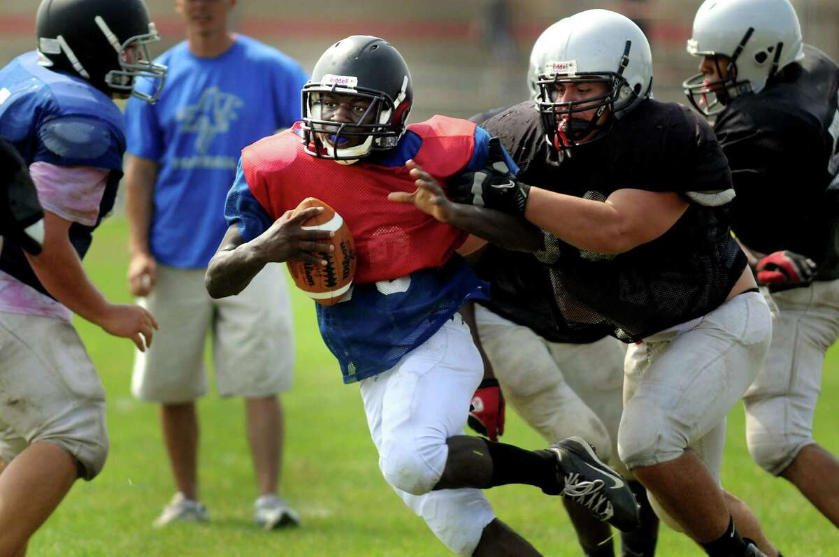 Albany quarterback Tyshen Morris, center, carries the ball as Niskayuna defends during a scrimmage on Saturday, Aug. 25, 2012, at Niskayuna High in Niskayuna, N.Y. (Cindy Schultz / Times Union)