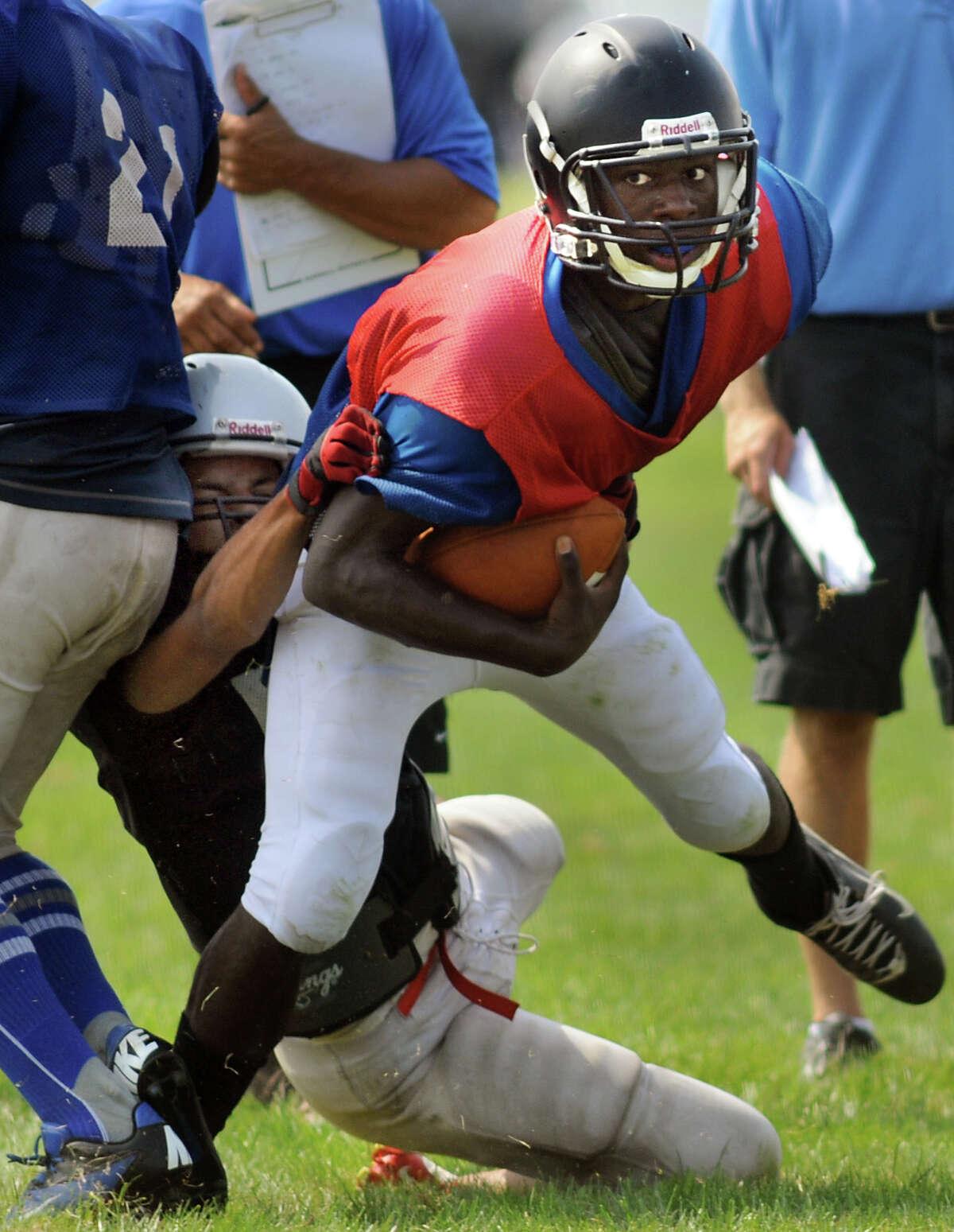 Albany quarterback Tyshen Morris, center, fights through a Niskayuna tackle during a scrimmage on Saturday, Aug. 25, 2012, at Niskayuna High in Niskayuna, N.Y. (Cindy Schultz / Times Union)