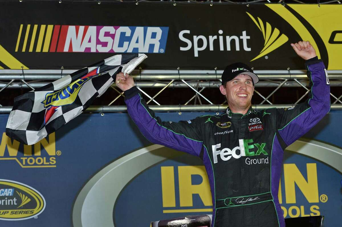 Denny Hamlin holds the checkered flag in victory lane after winning the NASCAR Sprint Cup Series auto race at Bristol Motor Speedway, Saturday, Aug. 25, 2012, in Bristol, Tenn. (AP Photo/Autostock, Brian Czobat) MANDATORY CREDIT