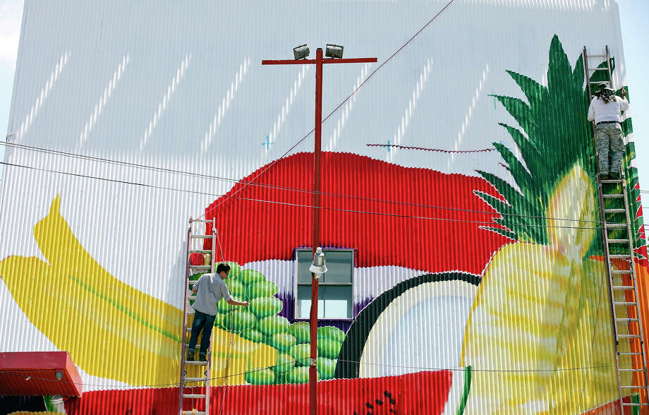 Freelance artists Alan Calvo, 26, (left) and Ronald Rocha, 72, paint a mural on the A-frame roof of Los Valles Fruits & Food Stand in the 6200 block of S. Flores Street Saturday Aug. 25, 2012. Rocha said the mural, which will include an American flag, would take a week and a half to complete. Photo: Edward A. Ornelas, San Antonio Express-News / © 2012 San Antonio Express-News