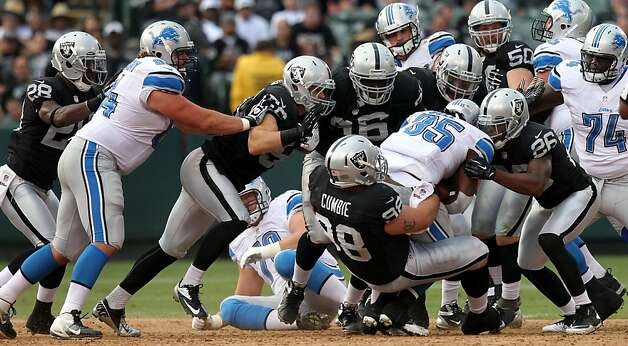 The Oakland Raiders defense gang tackle Detroit Lions Joique Bell in the 4th quarter of their NFL pre-season football game with the Detroit Lions at O.co Coliseum on Saturday August 25, 2012 in Oakland, California. Photo: Lance Iversen, The Chronicle
