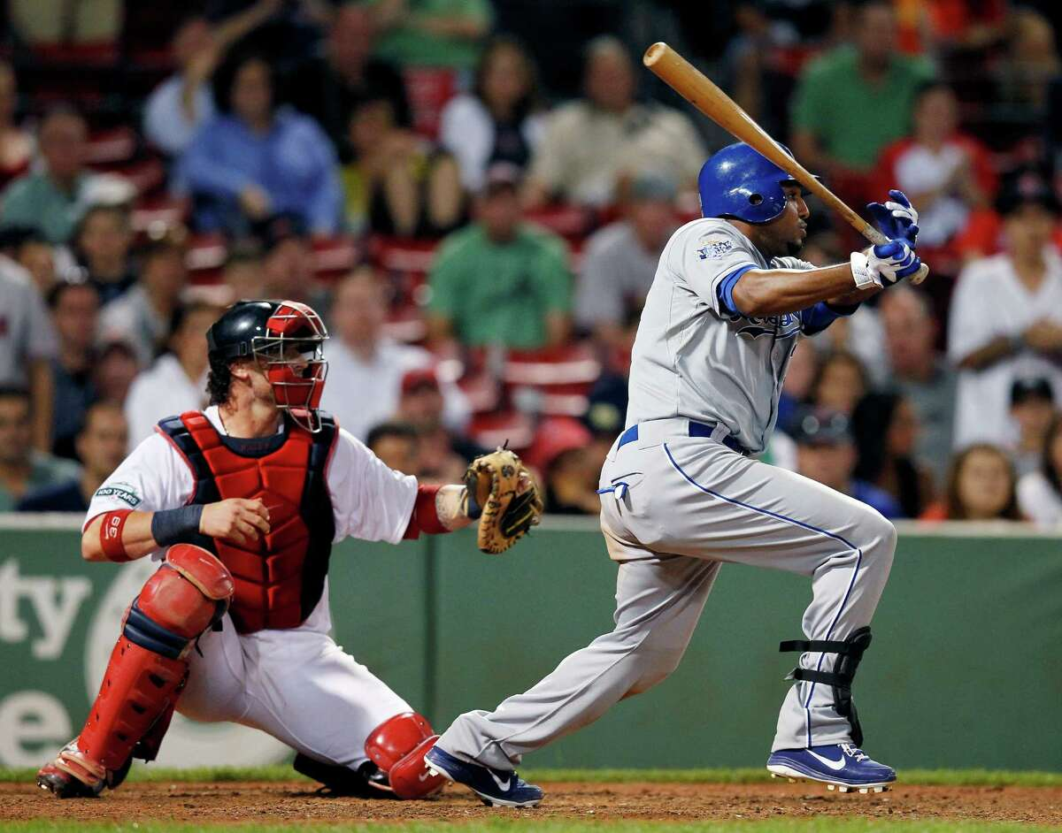 Kansas City Royals' Tony Abreu, right, follows through on an RBI single in front of Boston Red Sox's Jarrod Saltalamacchia in the 12th inning of a baseball game in Boston, Saturday, Aug. 25, 2012. The Royals won 10-9 in 12 innings. (AP Photo/Michael Dwyer)