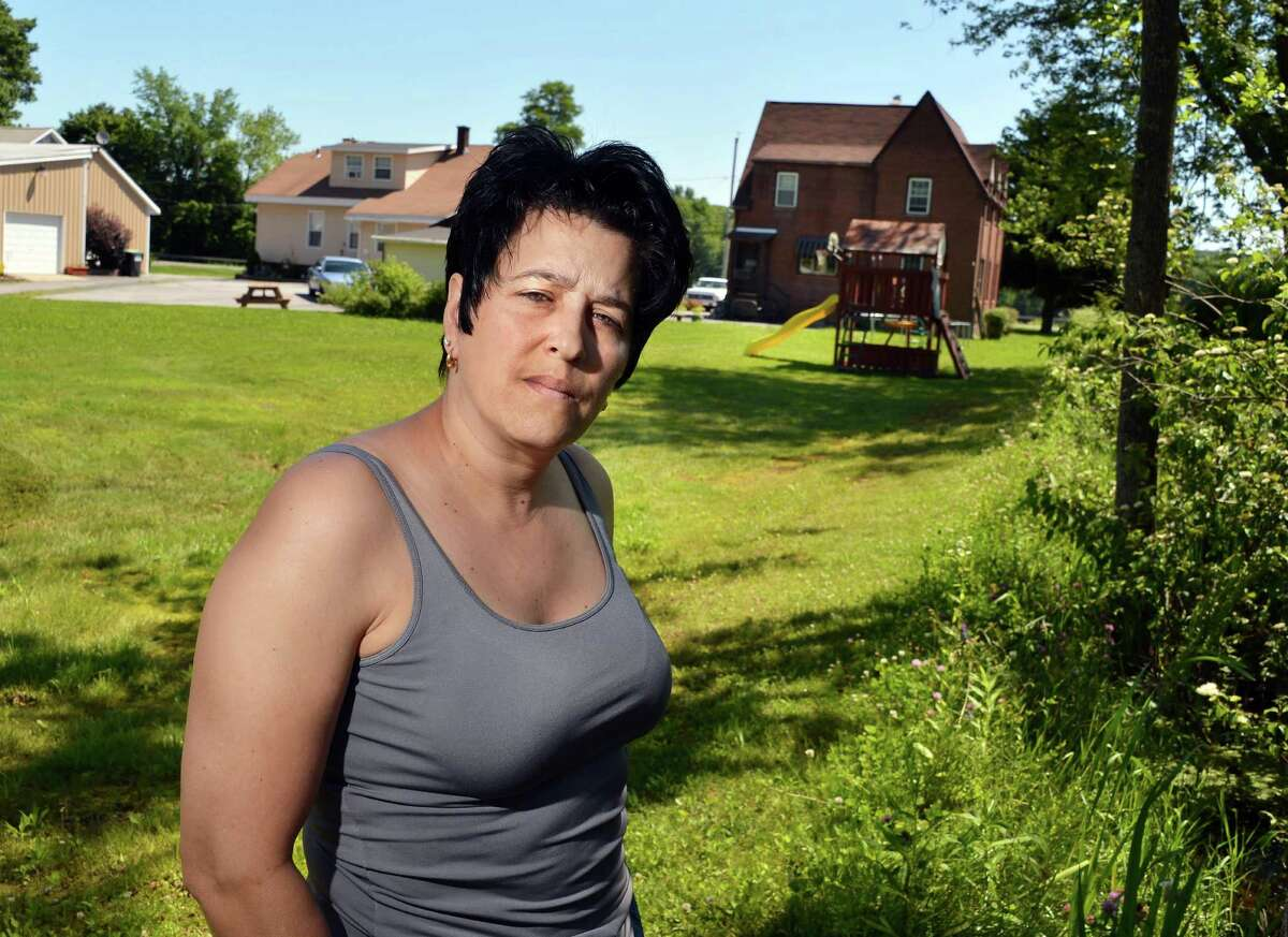 Amy DiModugno, of Halfmoon, said her backyard on Hudson River Road often floods when heavy rains strike. She has been cited by the U.S. Army Corps of Engineers for filling in part of her yard that's federal wetlands. A neighbor also is suing her for doing it. (John Carl D'Annibale / Times Union)