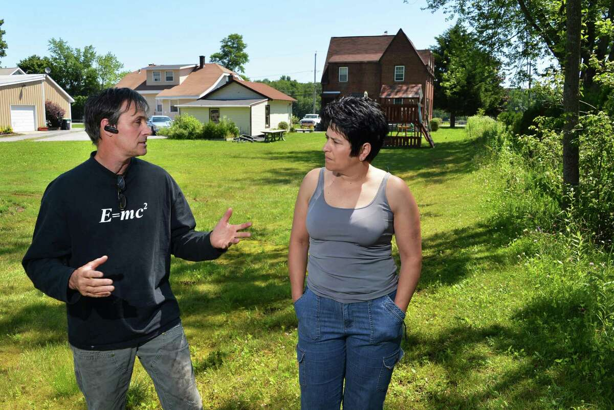Homeowners John Forino, left, and Amy DiModugno in their backyards in Halfmoon this summer. Forino says DiModugno is being targeted by the Army Corps for filling in her yard - something he said other residents in that area have done. (John Carl D'Annibale / Times Union)