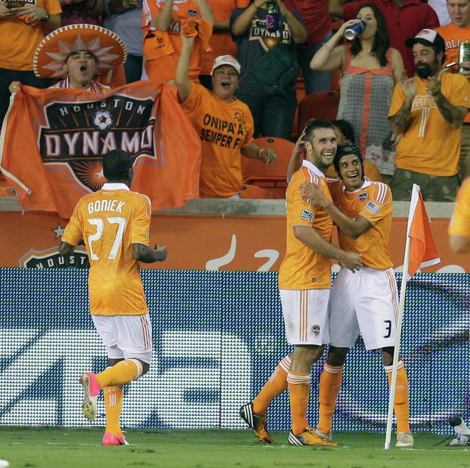 Will Bruin, center, celebrates with Calen Carr, right, and the Dynamo fans at BBVA Compass Stadium after Bruin struck in the 21st minute against Toronto FC on Saturday night. Toronto tied the match late. Photo: Bob Levey / 2012 Getty Images