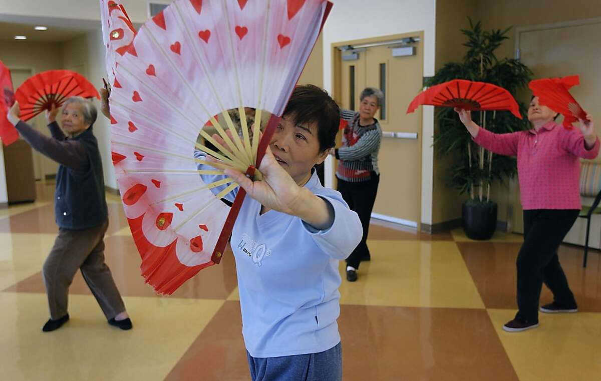 Anna Ou (center) and her students uses mulan fans during a Tai Chi class at the Evelyn Whitt senior housing center in San Francisco, Calif. on Friday, Aug. 24, 2012.